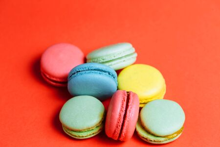 Closeup of sweet green, yellow, coral, blue macaroons on red background Banco de Imagens