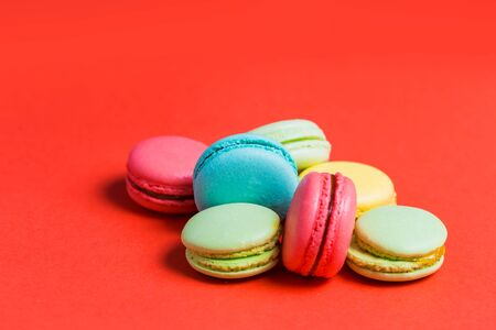 Close up of sweet green, yellow, coral, blue macaroons on red background. Fresh pastries, Breakfast, cafe concept