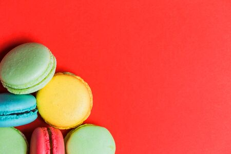 Closeup of red background for copy space with colorful macaroons in the corner. Sweet green, yellow, coral, blue French pastries Banco de Imagens