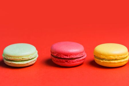 Close up of three French macaroons yellow, green and pink on a red background with copy space Banco de Imagens