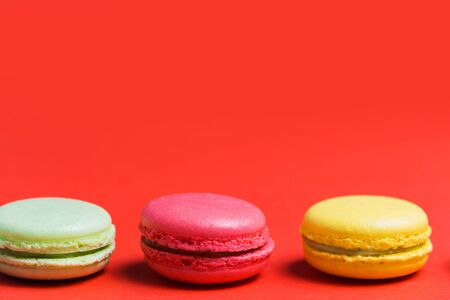 Close up of French macaroons on red background with copy space