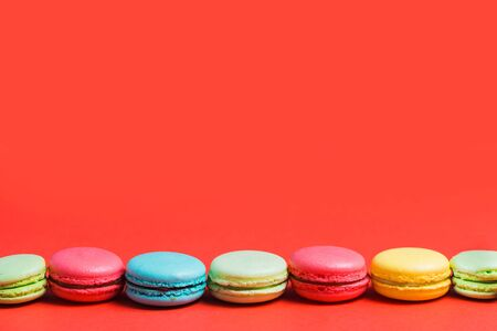 Bright red background for text with colorful yellow, green, blue, pink macaroons. Copy space for pastry chef, cafe, bakery Banco de Imagens