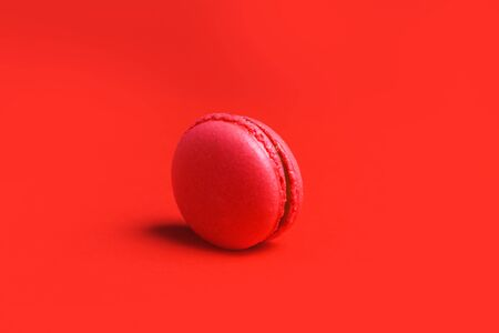 Minimalism. One coral or pink French macaroon on a red background, closeup