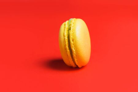 Closeup of one yellow sweet macaroon on red background. Sweet French pastries for tea
