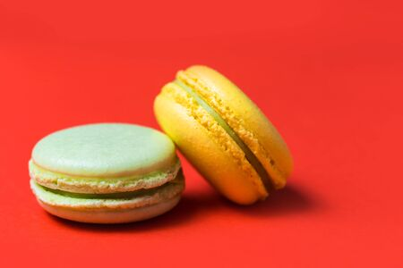 Closeup of two green and yellow French macaroons on a red background