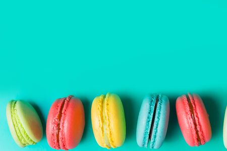 Beautiful fresh macaroon on turquoise background with copy space