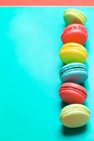 Beautiful turquoise vertical background with colorful macaroons and copy space, pastel colors.