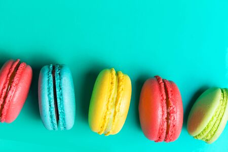 Beautiful fresh macaroon on turquoise background with copy space. Closeup
