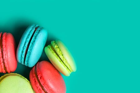 Close up of delicious fresh macaroon on turquoise background with copy space for confectioner, cafe, bakery Banco de Imagens