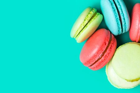 Sweet and colorful french macaroons on turquoise background with copy space, top view, closeup