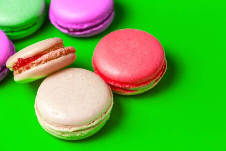 Closeup of colorful pink, purple macaroon on green background. Sweet pastries, Breakfast Banco de Imagens