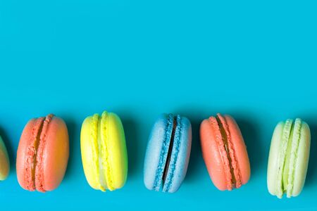 macaroon on blue background with copy space, pastel colors, top view. Yellow, coral, green French pastries, Breakfast
