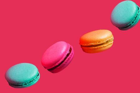 Different types of macaroons in motion falling on light pink background, closeup