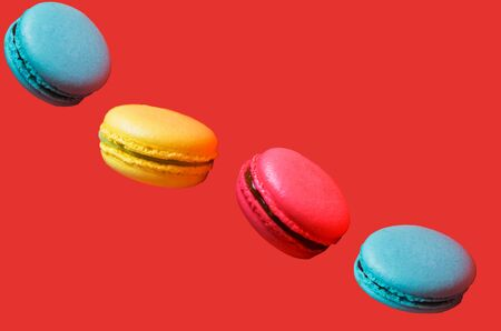 Different types of macaroons in motion falling on light pink colorful background, closeup