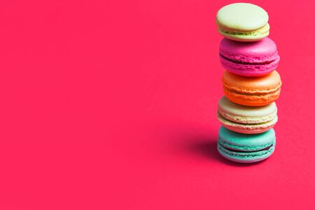 Bright pink background for text with colorful macaroons on the edge of the photo, copy space. Application for pastry chef, confectioner