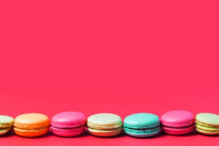 Bright pink background for text with colorful French macaroons, copy space.