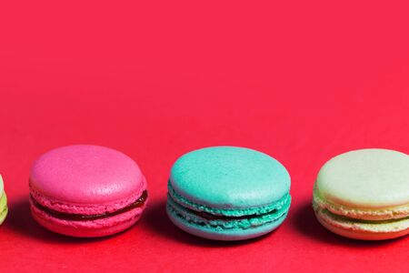 Close up of baked three multicolored macaroons on pink background, copy space.