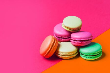 Cake colorful French macaron or macaroon on pink and orange background with copy space, closeup
