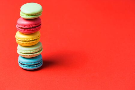 Bright red background for text with colorful macaroons on the edge of the photo, copy space