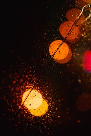 Black abstract background with bright colorful round bokeh with drops at night 写真素材