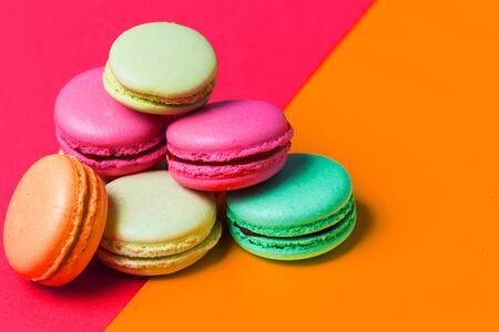 Bright pink and orange colored background for text with colorful macaroons on the edge of the photo, copy space. Application for pastry chef, confectioner