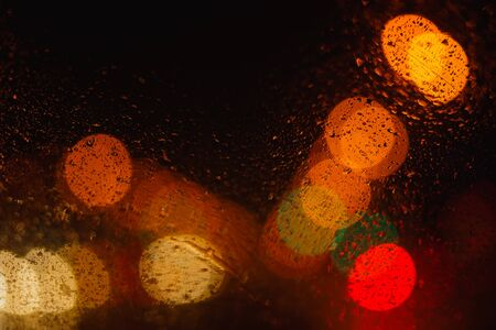 Blurred yellow bokeh with small drops on black background with copy space for text, texture, abstract 写真素材