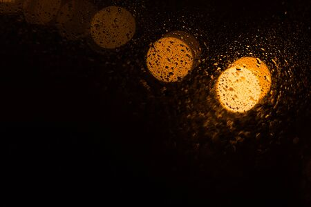 Beautiful black abstract background with yellow bokeh with drops. Texture for copy space