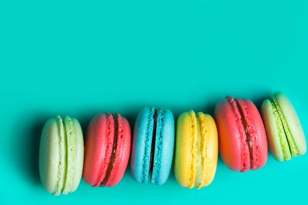 Cake a lot of colorful french cookies macaroons on turquoise background with copy space