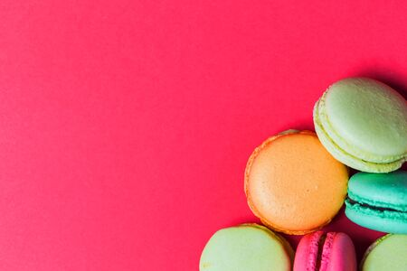 Beautiful bright pink background with French pastry macaroons, copy space.