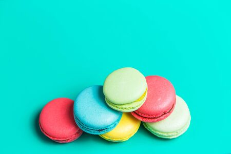 Cake blue, pink, yellow, green macaroon on turquoise background with copy space, top view. Sweet French pastries for tea