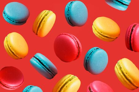 Different types of macaroons in motion falling on a pink background. Turquoise, orange sweet French pastries, closeup