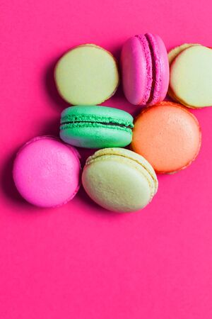 Flat lay of many colorful macaroons on on pink background, top view