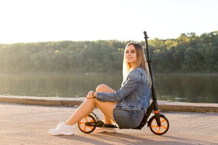 Beautiful blonde woman in denim clothes sits on her scooter and smiles at the camera on the waterfront street