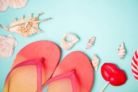 Bright flip flops with seashells and red lollipops in shape of lips on mint background. Flat lay composition. Beach, summer, holiday, sea, vacation concept Stock Photo