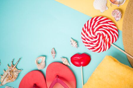 Beach accessories on sky blue and yellow background with copy space. Flat lay composition of pink flip flops, seashells, towel, hat, sunglasses and two lollipops. Summer, holiday, vacation concept.