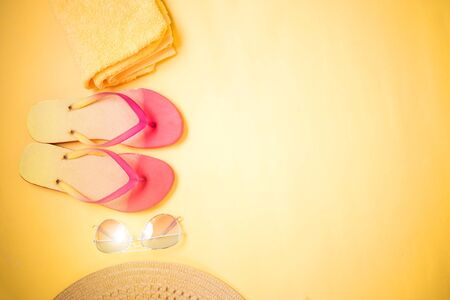 Beige straw sun hat, sunglasses, towel, colorful flip flops on yellow background with copy space. Stock Photo