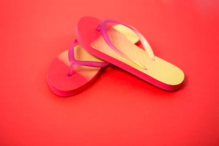 Yellow pink sandals on coral background.