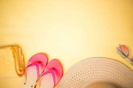 Flat lay of beige straw sun hat, sunglasses, towel, pink flip flops on pastel yellow background. Stock Photo