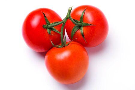 Gros plan de trois tomates fraîches rouges dans un tas dans une tige verte sur fond blanc isolé, vue de dessus. Banque d'images