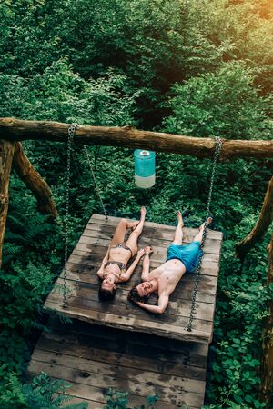 Beautiful couple enjoying the nature in the forest on a swing