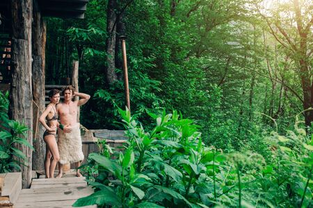 A young couple in lingerie in a green beautiful forest stand and look at the camera. Spa, bathing, relaxation, rest concepts
