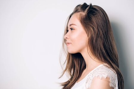 Portrait of girl in profile. Beautiful woman has a clean well-groomed skin and long straight hair. Close-up portrait against a light gray background.