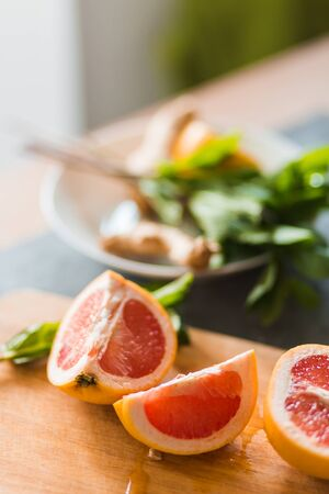 Closeup of ripe citrus pieces on wooden Board. Red grapefruit, lime, lemon on the kitchen table with mint. Healthy food, vitamins, summer concept Standard-Bild