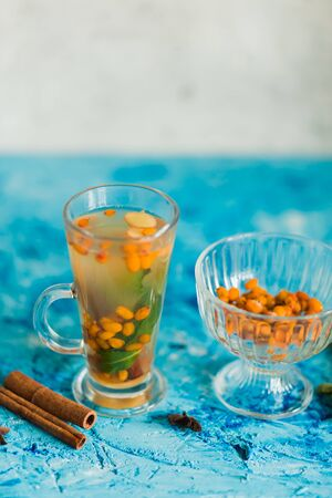 Delicious sea buckthorn tea with cinnamon, lemon and lime, mint on the blue table in the kitchen, copy space. Proper nutrition, delicious food