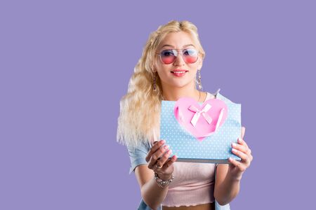 Beautiful stylish interested blonde woman wearing denim shirt, pink t shirt, sunglasses, jewellery looking inside shopping bags, opening present on violet background. Sale, gift, holiday concept. Stock Photo