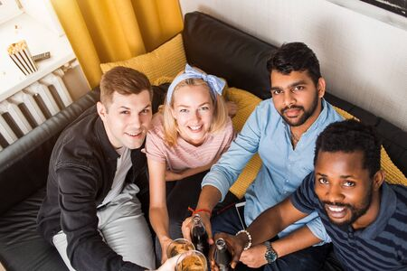 Top view of happy cheerful multi ethnic friends in casual clothes sitting on couch clinking bottles and glasses of drinks smiling looking at camera. Celebration, people and holidays concept.