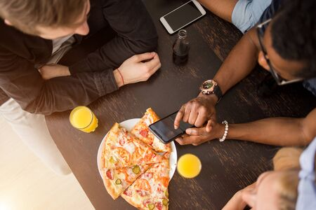 Top view of group of multiracial friends sitting around table, having lunch, eating pizza, drinking juice, using mobile phone. Delivery, food, technology concept. Stock fotó