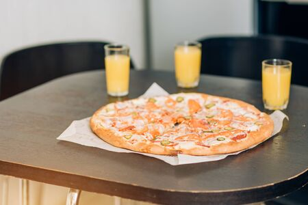 Delicious pizza and three glasses of orange juice on table. Cropped shot of man pouring drinks into glass. Selective focus. Food concept.