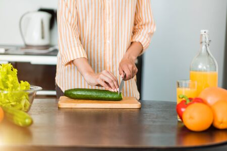 Cropped shot of caucasian woman cooking in kitchen. Closeup of female hands slicing cucumber on wooden chopping board. Fresh vegetables and fruits, orange juice on table.