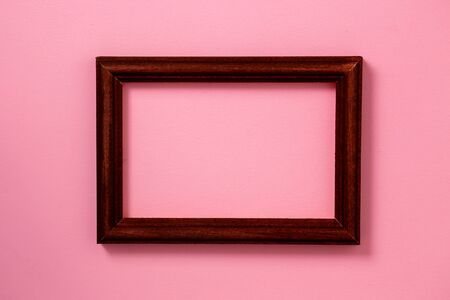 One dark brown wooden photo frame with copy space on pastel pink paper background